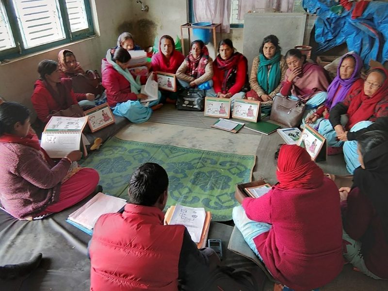 A group of 14 Nepalese women and 1 man sit in a circle on a green carpet. Most are wearing red and headscarves.