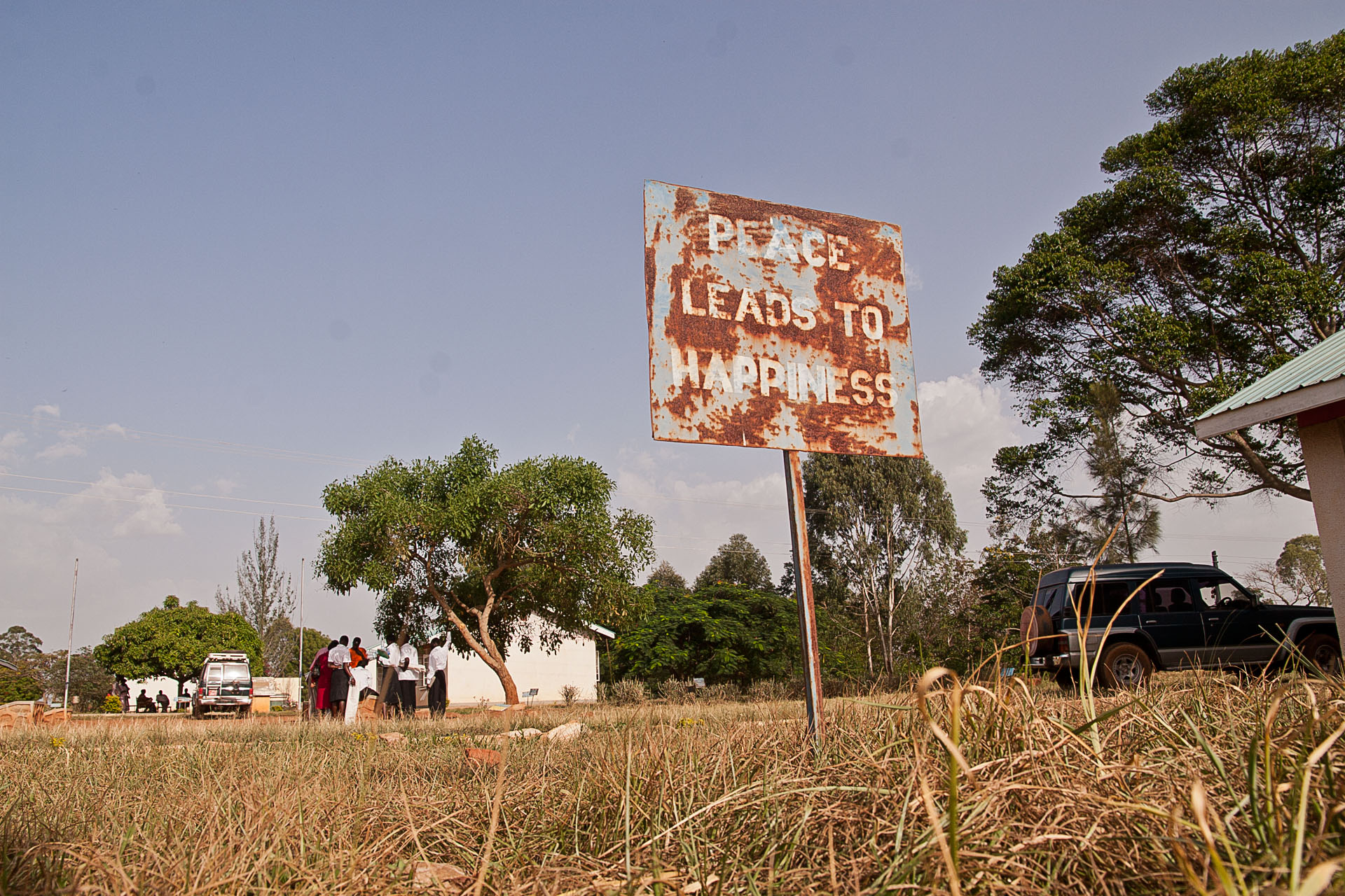 Rusty roadside sign that reads 'peace will make us happy'