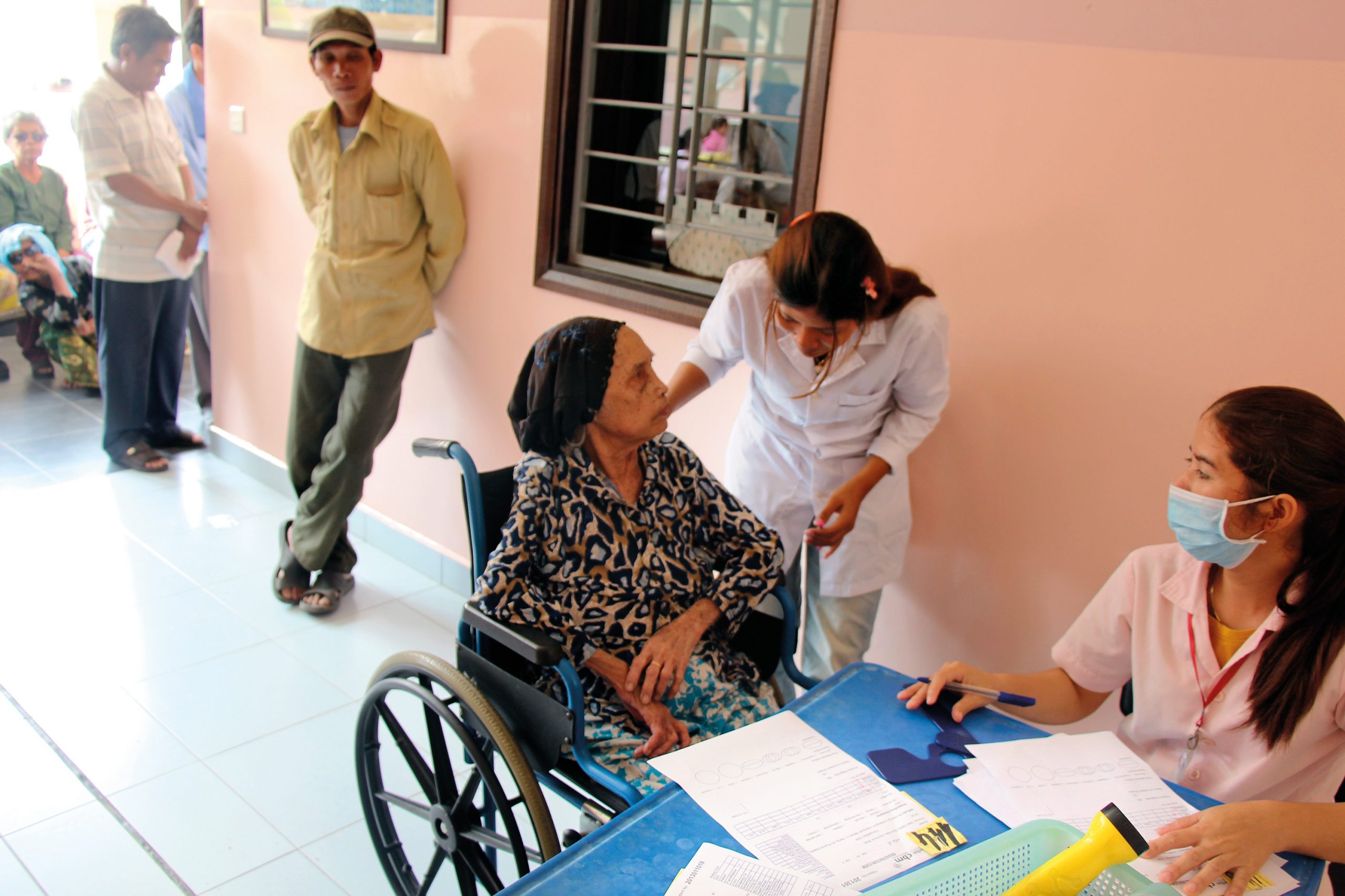 Old lady in a wheelchair being tended to by two nurses