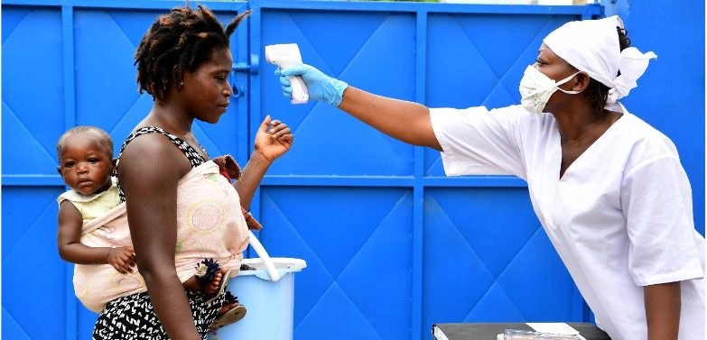A female African medic in white PPE points a digital thermometer at an African mother with a baby on her back