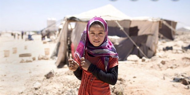 A girl in headscarf stands in front of tents in a desert landscape