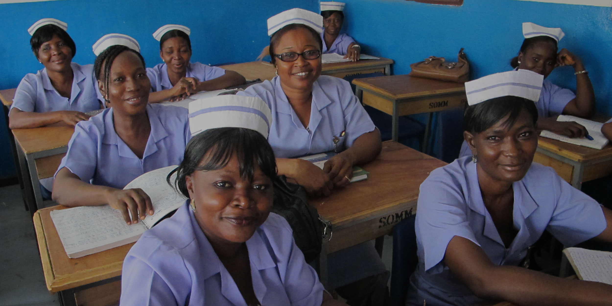 A group of seated African female nurses in uniform, smiling at the camera