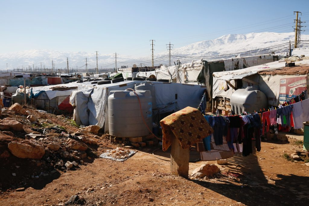 A scene of white tents, water tanks, washing lines and power lines with snowy mountains in the distance