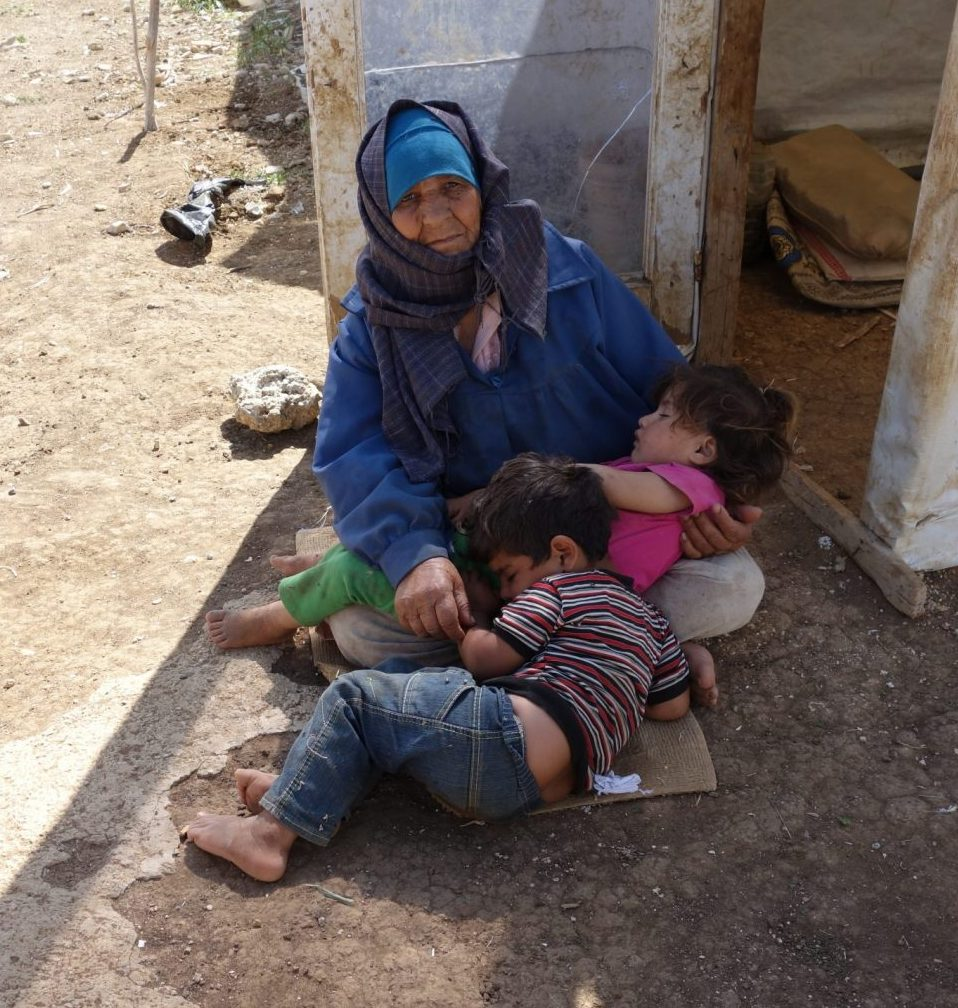 Old woman in blue headscarf sitting on the ground cradling a sleeping girl and boy