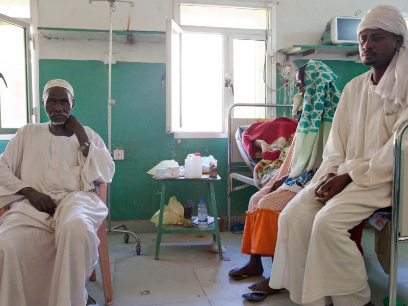 An African women and man sit on a hospital bed while a man sits on a chair, staring at the camera