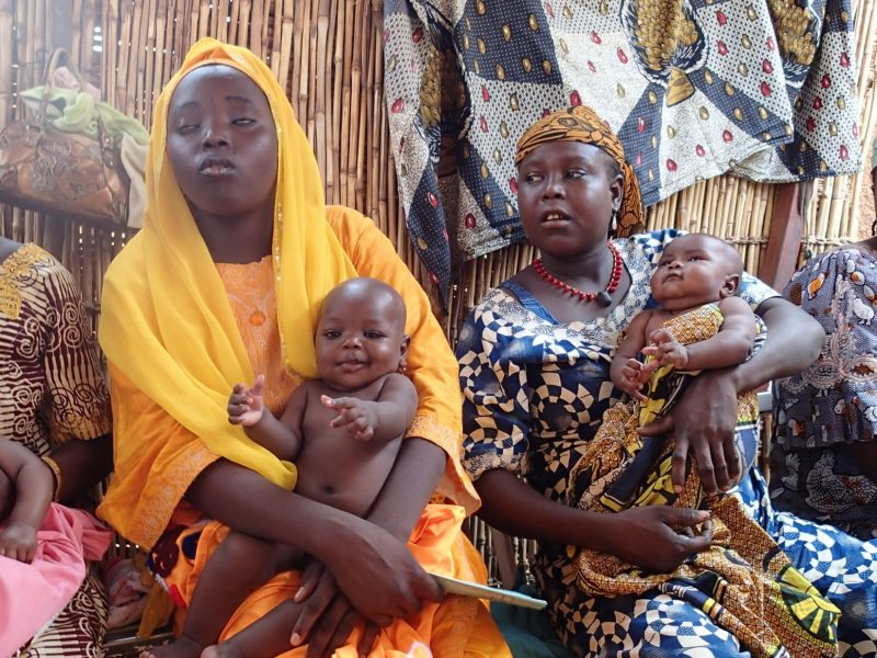 Four African women in brightly coloured clothes sitting waiting, each with a baby on their knee