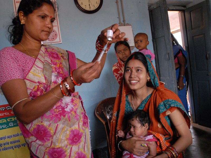 Standing Indian woman files a syringe while a seated mother and her baby look on