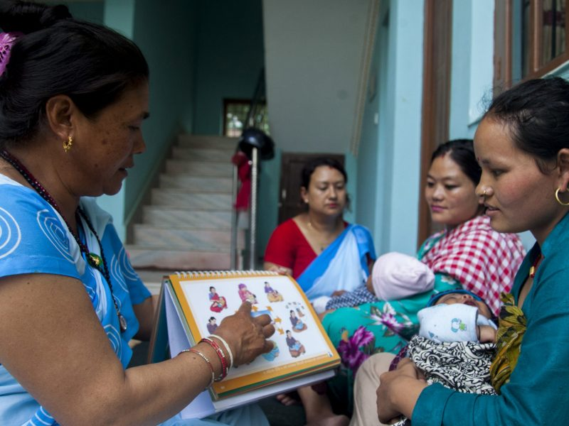 A woman in pale blue sari shows diagrams to a mother holding a baby