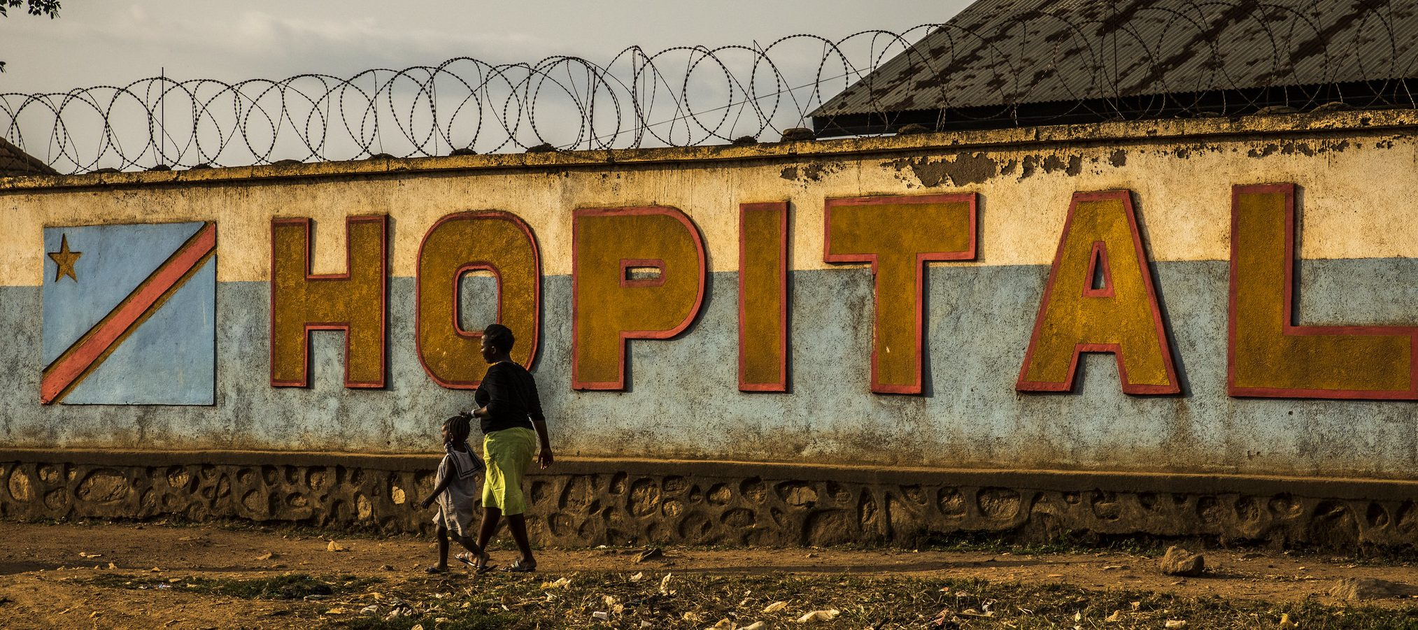 An African woman and small child walk past a wall with the word 'HOPITAL' and barbed wire across the top