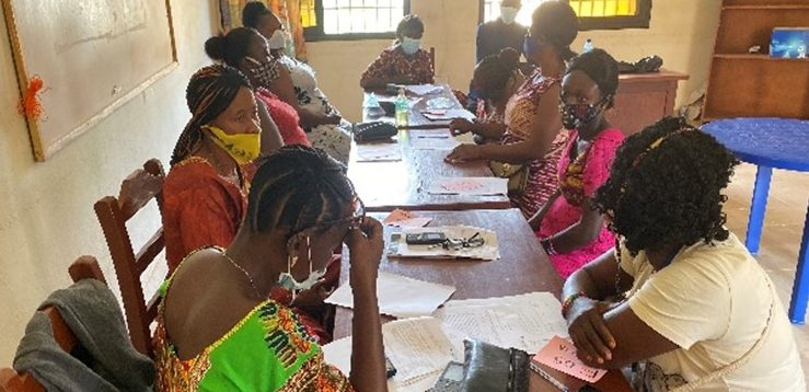 A group of African women sitting round a table reading documents and talking